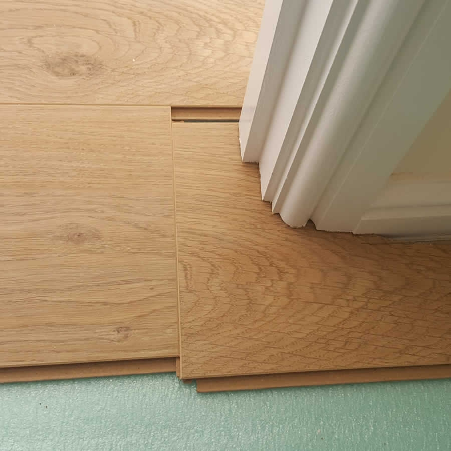 Preparing the laminate board around a door to slide under with covered expansion gap
